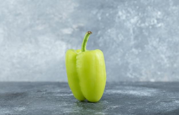 Close-up foto van biologische groene paprika op grijze achtergrond.
