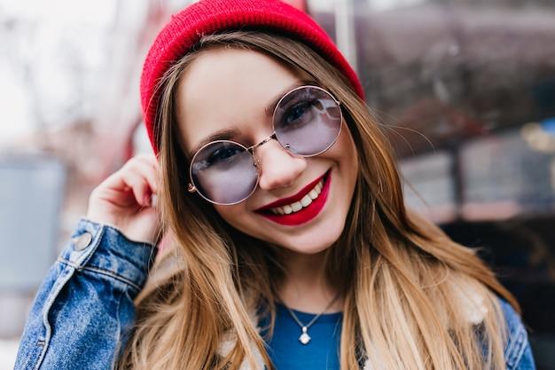 Close-up foto van blank meisje ontspannen in de stad in het lenteweekend. buiten schot van prachtige europese dame in spijkerjasje en blauwe bril.