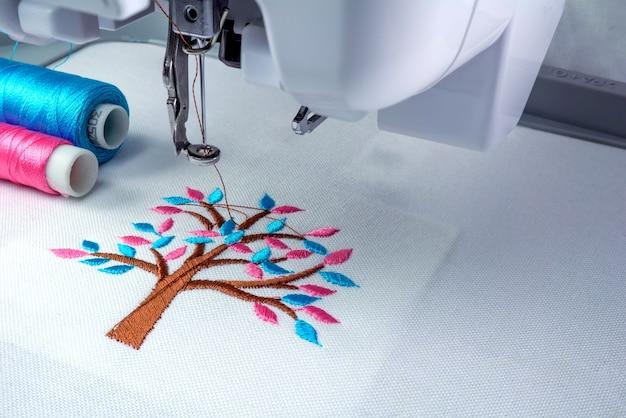Close-up foto van borduurmachine en twee draden cyaan en roze kleur.