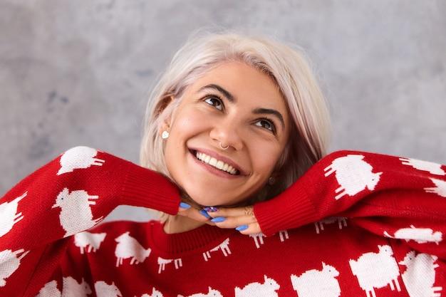 Close-up foto van charmante modieuze jonge europese vrouw in stijlvolle rode gebreide trui dromen of denken over iets leuks, opzoeken met stralende brede glimlach, hand in hand onder de kin