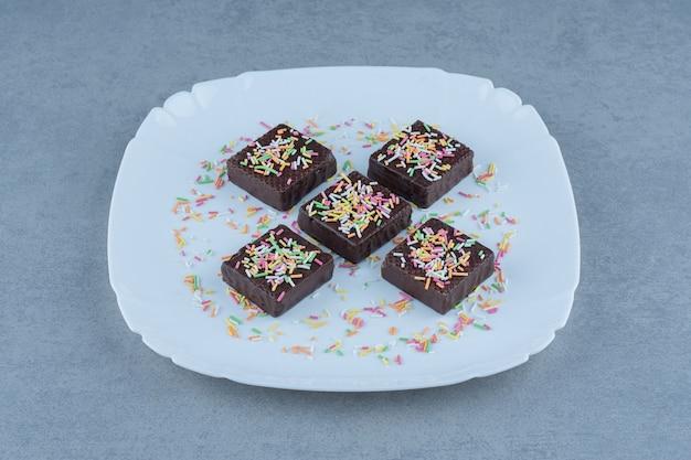 Close-up foto van chocolade wafels met strooi op witte plaat.