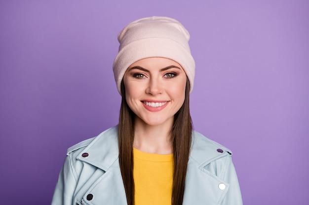 Close-up foto van cool stijlvol goed humeur mooie dame blij warm lenteweer straat kleding glimlachend witte tanden dragen casual hoed blauwe moderne stijl jas geïsoleerde paarse kleur achtergrond