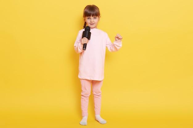 Close-up foto van coole aantrekkelijke dame jongen met plezier, staande geïsoleerd op gele achtergrond, schattig kind met microfoon concert regelen, jurken bleke roze achtergrond.