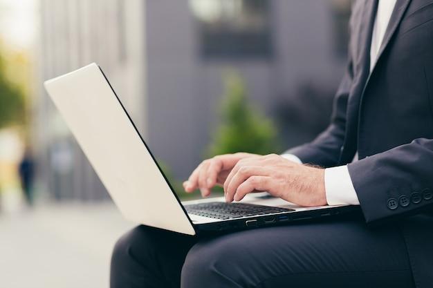 Close-up foto van de hand van een mannelijke zakenman in een pak die op een witte laptop werkt