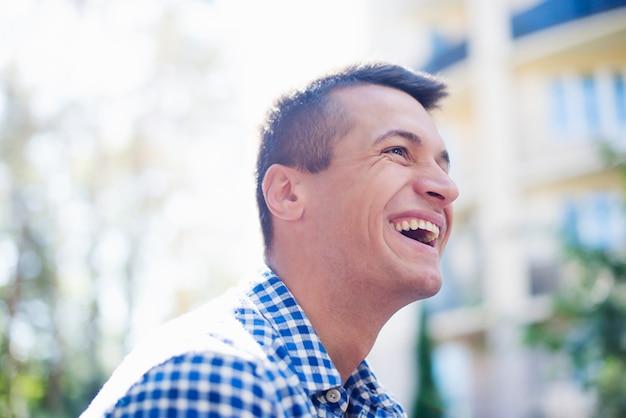 Close-up foto van de jonge knappe gelukkig man in een geruit overhemd terwijl lacht buitenshuis