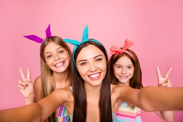 Close-up foto van drie mensen in hoofdbanden maken v-signs selfie dragen jurk rok geïsoleerd op roze achtergrond