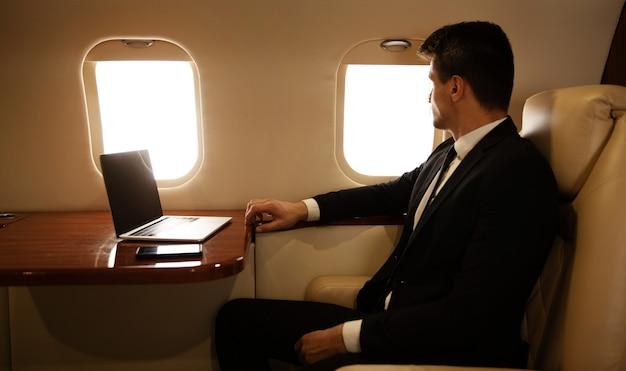 Close-up foto van een aantrekkelijke man in een pak, die in profiel op zijn stoel bij het raam in het vliegtuig zit
