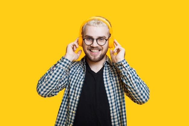 Close-up foto van een bebaarde blanke man met blond haar met koptelefoon en bril poseren op een gele muur