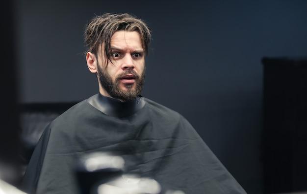 Close-up foto van een bebaarde man met rommelig haar die naar zijn spiegelbeeld in een kapperszaak kijkt met een bange gezichtsuitdrukking.