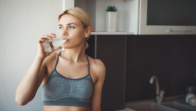 Close-up foto van een blanke vrouw drinkwater na het oefenen van thuisfitness