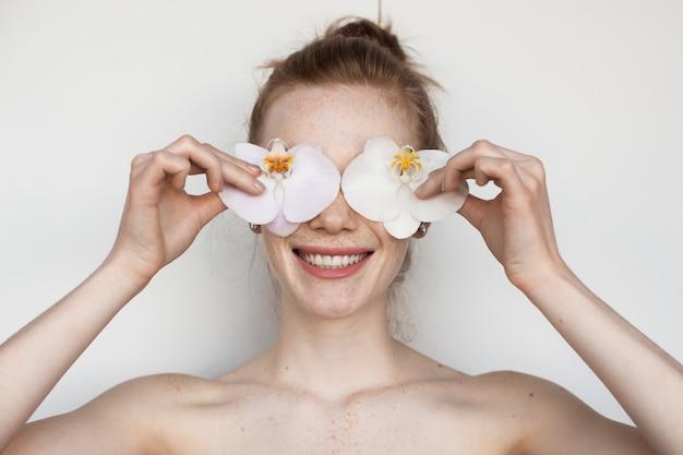 Close-up foto van een blanke vrouw met ongeklede schouders die haar ogen bedekken met bloemen en toothily glimlach