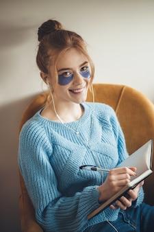Close-up foto van een blanke vrouw met ooglapjes en sproeten die lacht terwijl ze naar muziek luistert en iets in het boek schrijft