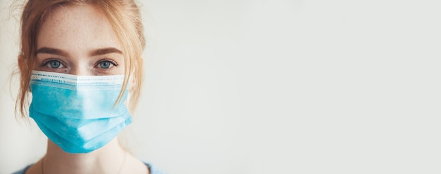 Close-up foto van een blanke vrouw met sproeten en gemberhaar die een blauw medisch masker draagt tijdens de lockdown