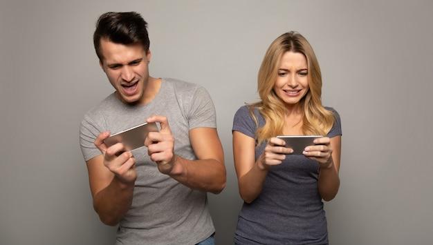 Close-up foto van een blond meisje en haar knappe vriendje, die mobiele games spelen op hun smartphones met geconcentreerde gezichtsuitdrukkingen.