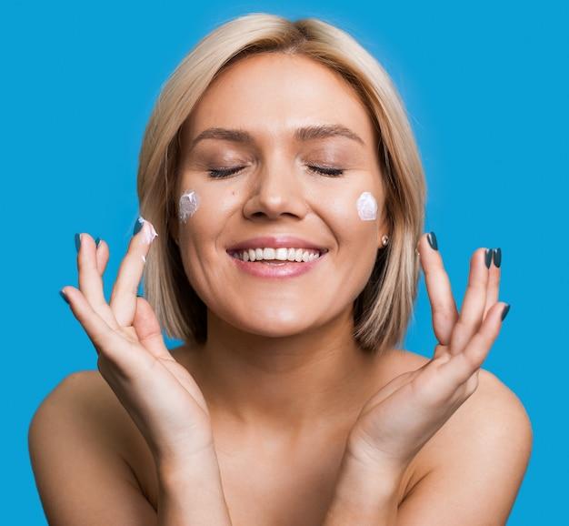 Close-up foto van een blonde dame met naakte schouders die een crème op haar gezicht aanbrengt die zich voordeed op een blauwe studiomuur