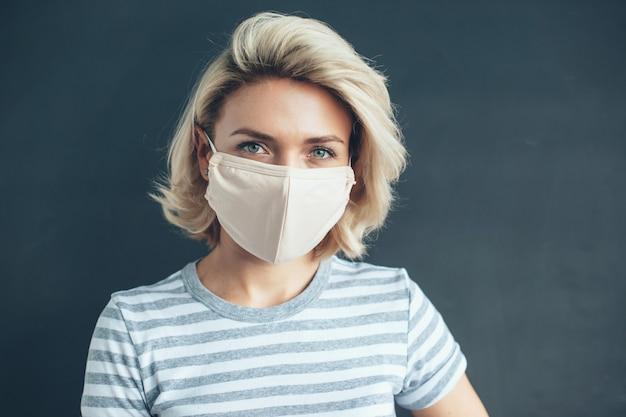 Close-up foto van een blonde vrouw met medisch masker op gezicht camera kijken