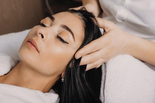 Close-up foto van een brunette blanke vrouw liggend met gesloten ogen terwijl het hebben van een hoofdmassage in de spa salon