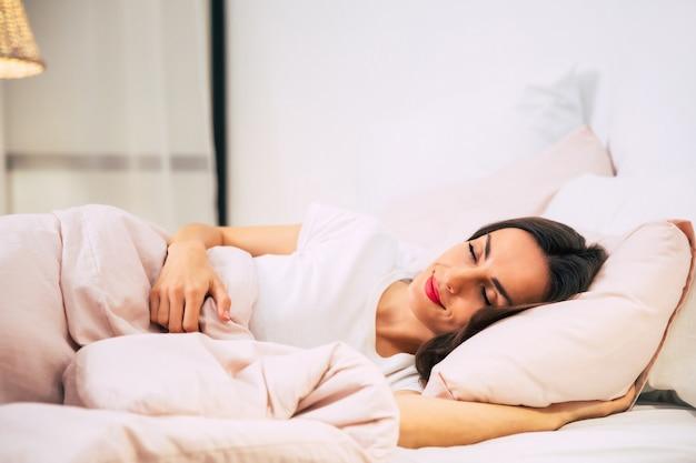 Close-up foto van een buitengewoon mooi meisje, dat lacht terwijl ze stevig slaapt in haar bed met het roze gekleurde beddengoed.