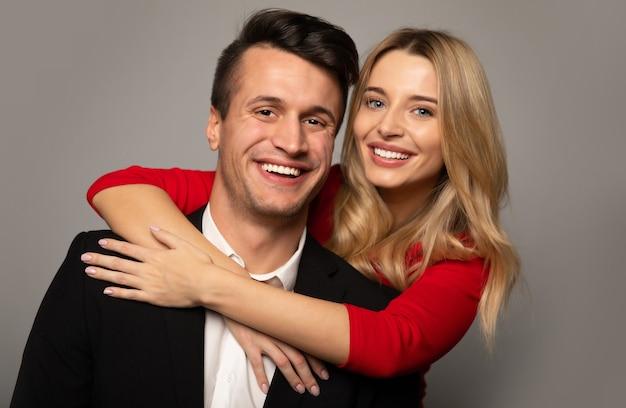 Close-up foto van een charmant blond meisje in een rode jurk, die haar vriendje in een pak vanaf de achterkant knuffelt, in de camera kijkt en glimlacht.