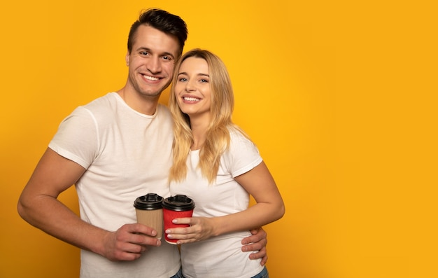 Close-up foto van een charmant stel in witte t-shirts, die hun koffiekopjes vasthouden, dicht bij elkaar staan en er gelukkig uitzien in de camera.
