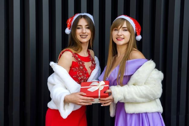 Close-up foto van een gelukkige brunette vrouw die een geschenkdoos geeft aan haar vriend op nieuwjaarsviering