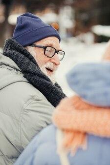 Close-up foto van een gelukkige oudere man in winterkleren die zijn hoofd naar de vrouw draait en naar haar glimlacht