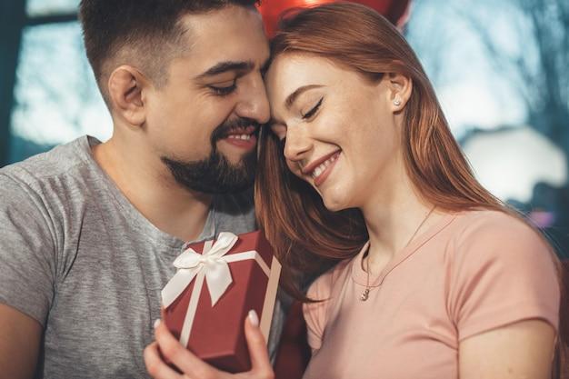 Close-up foto van een gember dame met sproeten met een cadeau van haar minnaar en glimlach samen omhelzen