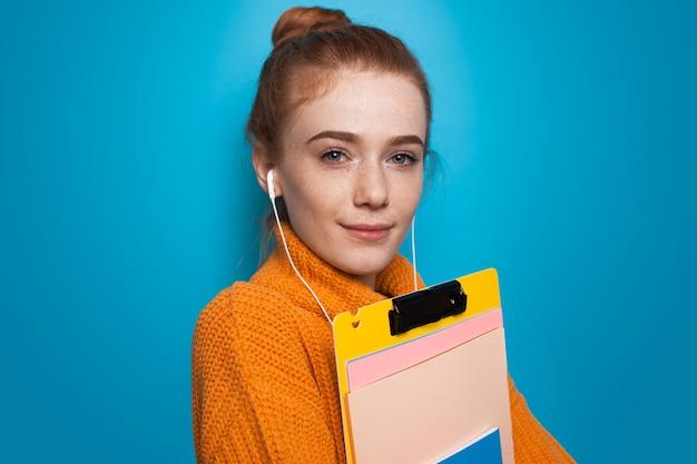 Close-up foto van een gember student met sproeten poseren met mappen en oortelefoons op een blauwe studiomuur in een gele trui