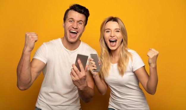 Close-up foto van een grappige man en een gelukkige vrouw, die schreeuwen van geluk, smartphones in hun handen houden en vuisten tonen als een teken van succes.