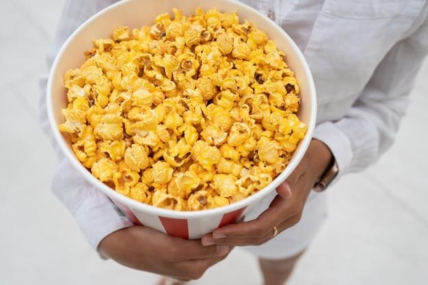 Close-up foto van een jong lief meisje, dat een tube popcorn in haar handen houdt.