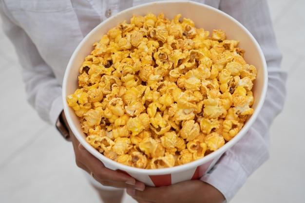Close-up foto van een jong lief meisje, dat een tube popcorn in haar handen houdt. Premium Foto
