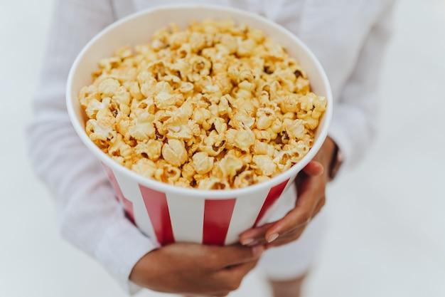 Close-up foto van een jong lief meisje, die een tube popcorn in haar handen houdt.