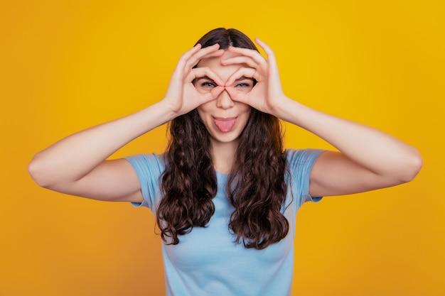 Close-up foto van een jong vrolijk meisje, blije positieve glimlach, laat een goed teken zien, gek met tong uit geïsoleerde gele achtergrond