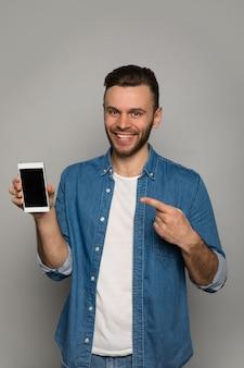 Close-up foto van een jonge man met een brede glimlach, die een smartphone in zijn rechterhand houdt, terwijl hij ernaar wijst met zijn linker wijsvinger.