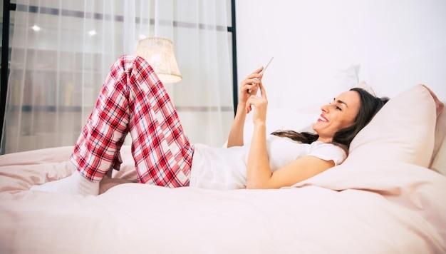 Close-up foto van een jonge vrouw in geruite pyjama, die rust in haar bed en glimlacht terwijl ze op internet op haar smartphone surft.