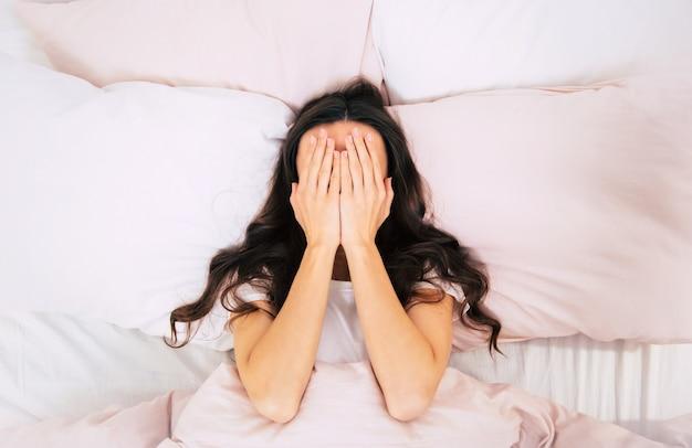 Close-up foto van een jonge vrouw met krullend bruin haar, die in haar bed op roze kussens ligt en haar gezicht bedekt met handpalmen.