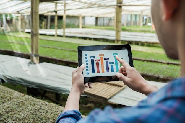 Close-up foto van een jonge zakenman met een tablet en een vinger die naar het scherm wijst