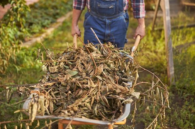 Close-up foto van een kar vol gebladerte en droog onkruid die door een tuinman wordt geduwd