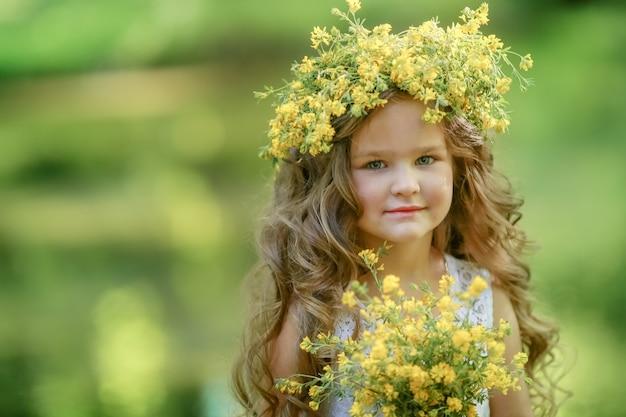Close-up foto van een kind met een boeket gele bloemen in zijn handen en een gele krans op zijn hoofd
