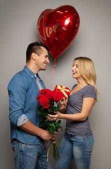Close-up foto van een lief stel, die st. valentijnsdag viert door cadeaus aan elkaar te geven en te glimlachen van geluk.