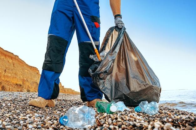 Close-up foto van een man die vuilnis verzamelt met een grijpgereedschap op het strand in de buurt van de oceaan