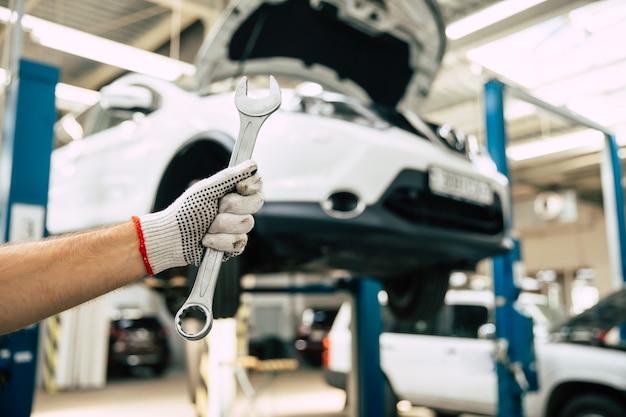 Close-up foto van een mannelijke automonteurs hand met een steeksleutel op de achtergrond van het repareren van een auto
