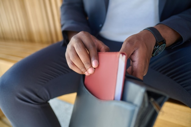 Close-up foto van een mans handen met een notitieboekje