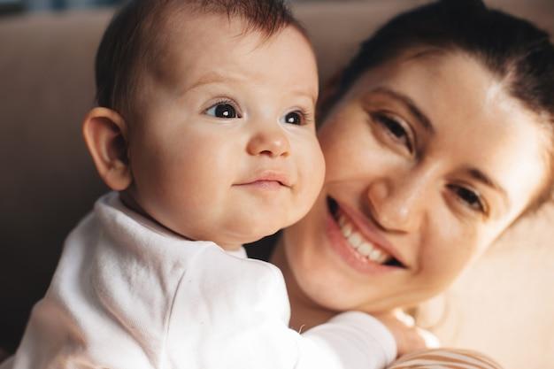 Close-up foto van een moeder met sproeten die trots naar de camera glimlacht en haar dochtertje vasthoudt