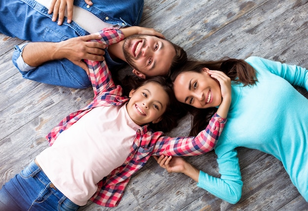 Close-up foto van een mooi jong gezin dat van kop tot kop op de grond ligt, breed glimlacht en samen knuffelt