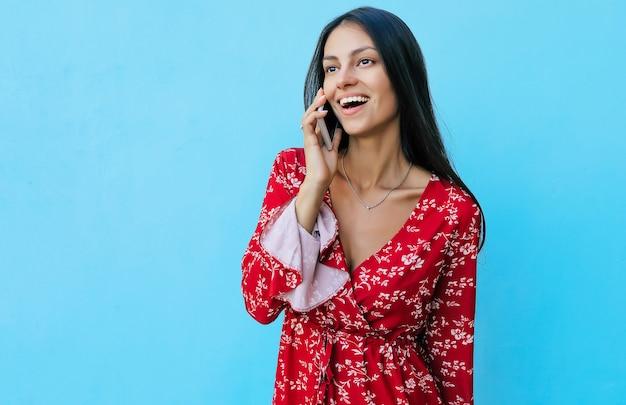Close-up foto van een mooi jong meisje met gitzwart haar, gekleed in rode zomeroutfit en glimlachend tijdens het telefoneren