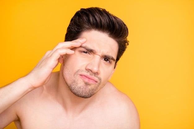 Close-up foto van een ongelukkige, overstuur man die observeert dat hij ouder wordt met rimpels op zijn gezicht geïsoleerd naakt over levendige kleurenmuur