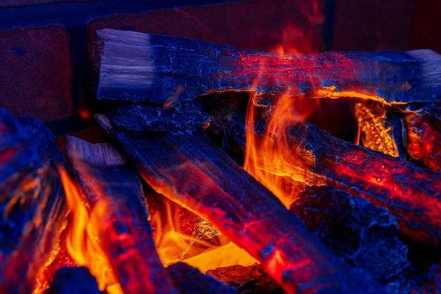 Close-up foto van een open haard met brandende houtblokken binnen