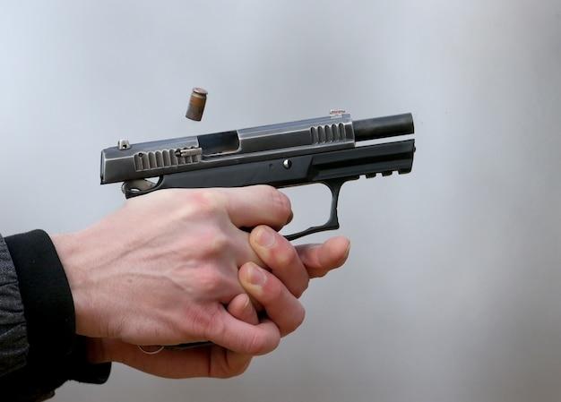 Close-up foto van een pistool schieten met twee handen, de schelpen afkomstig van de sluiter en blauwe rook.