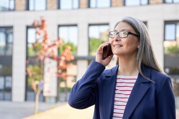 Close-up foto van een positieve grijsharige vrouw met een bril die een telefoongesprek voert